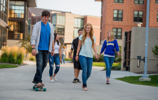 Students walking and skateboarding on campus